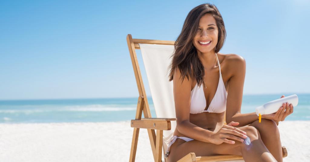Mujer joven sentada en una silla en la playa se echa proteccion solar en el cuerpo