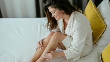 Mujer joven aparece en su cama con un albornoz blanco mientras se echa crema hidratante en las piernas y sonrie