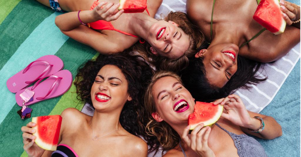 grupo de chicas en bikini y tumnadas en una toalla comen sandia y se rien