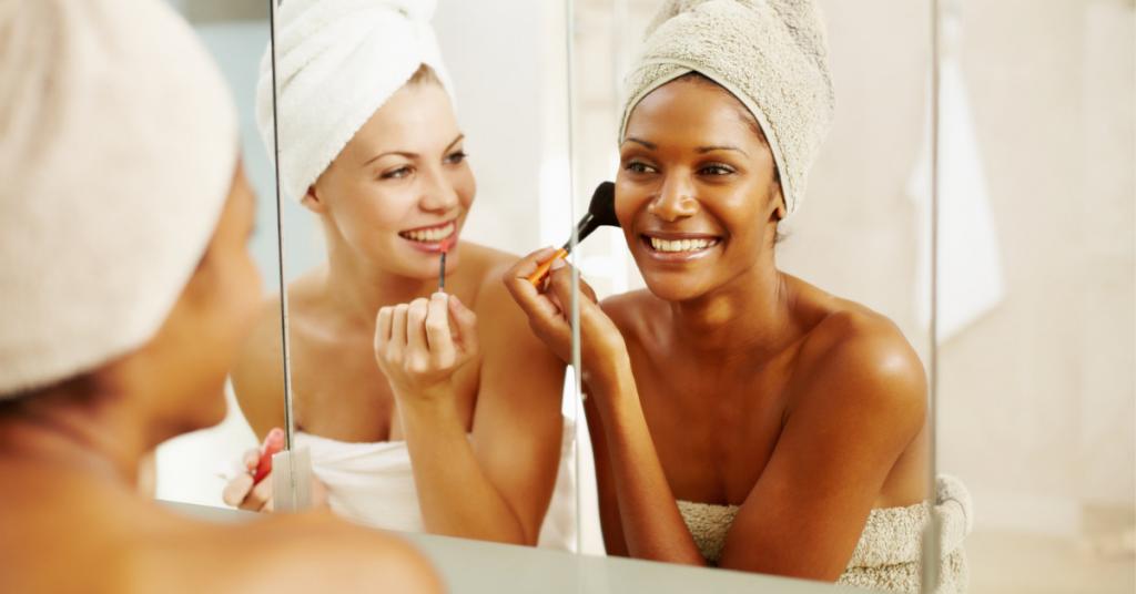 dos chicas frente al espejo llevan la toalla en el cuerpo y la toalla en la cabeza se maquillan y rien