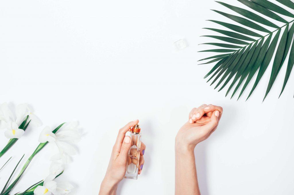 las manos de una chica con las uñas pintadas en color rosa claro se echa perfume en la muñeca y tambiem aparece una hoja de palmera y unas flores blancas sobre fondo blanco