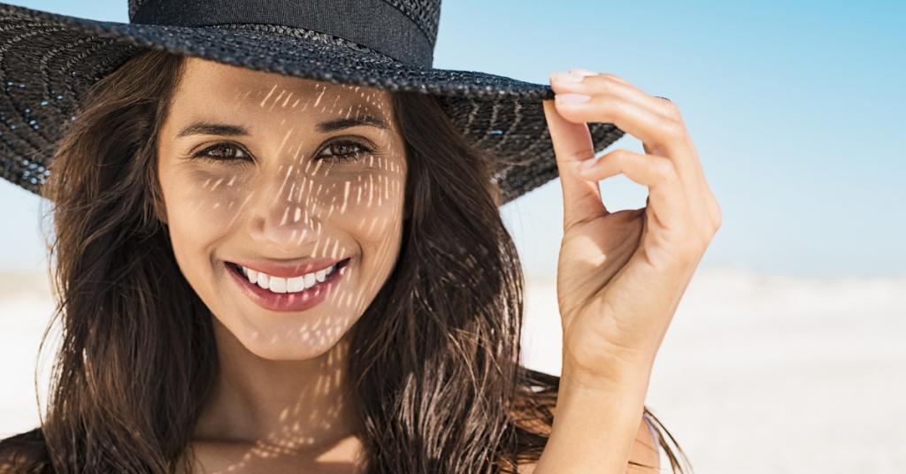 Una chica sonrie en la playa y lleva un somprero tipo pamela de color negro