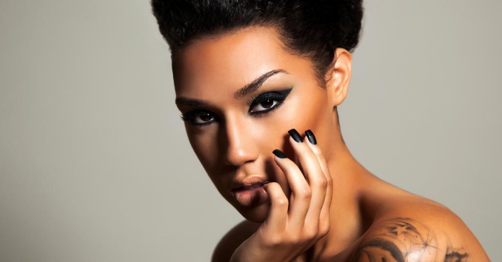 Chica de color mira a camara lleva un maquilaje muy rockero con ojos negros y uñas pintadas tambien en negro