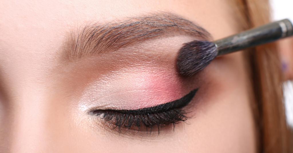 primer plano de un ojo maquillado con sombras en tonos rosas y claros la brocha sigue maquillando el extremo exterior del ojo