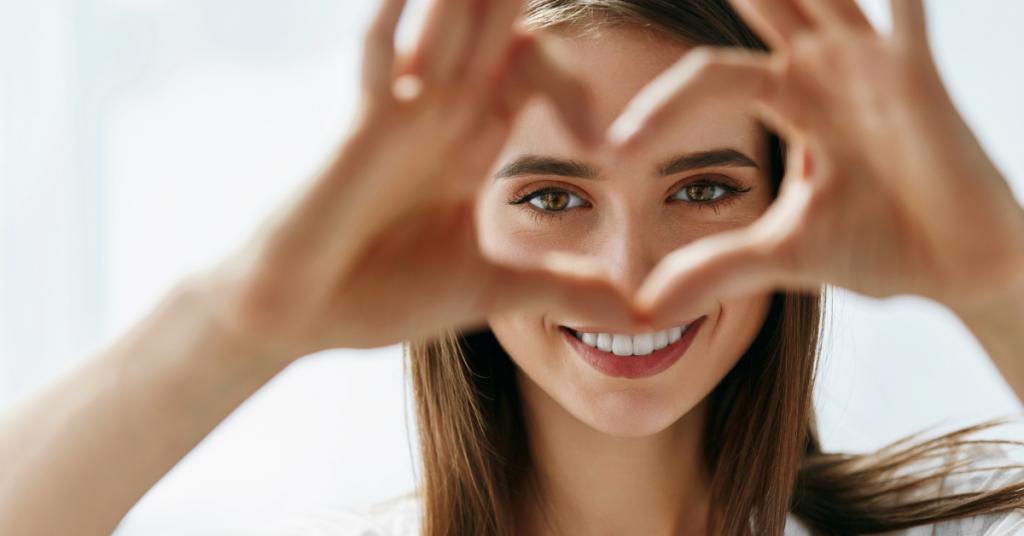 una chica mira a camara y sonrie con las manos hace la forma de un corazon y las situa frente a sus ojos