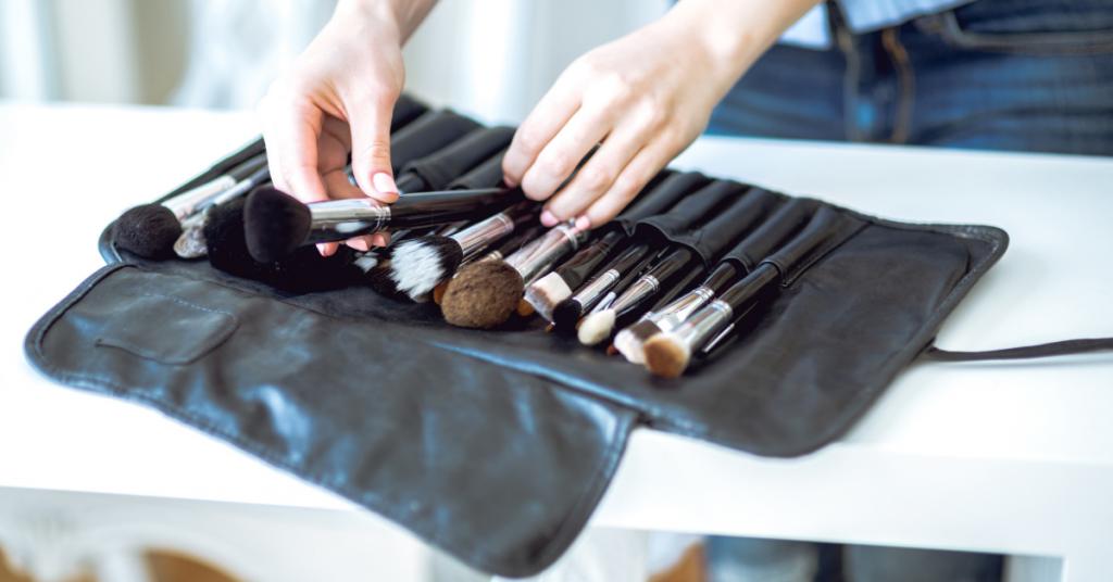 set de brochas de maquillaje dentro de un neceser negro y unas manos que sacan una de ellas