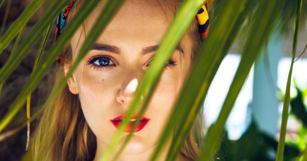 a traves de unas hojas de palmera vemos el rostro de una chica joven y con el rostro serio lleva los ojos pintados y los labios tambien de rojo