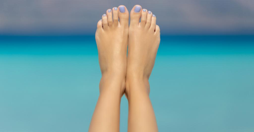 unos pies en alto sobre un fondo que es el mar azul lleva las uñas pintadas en un tono azul pastel