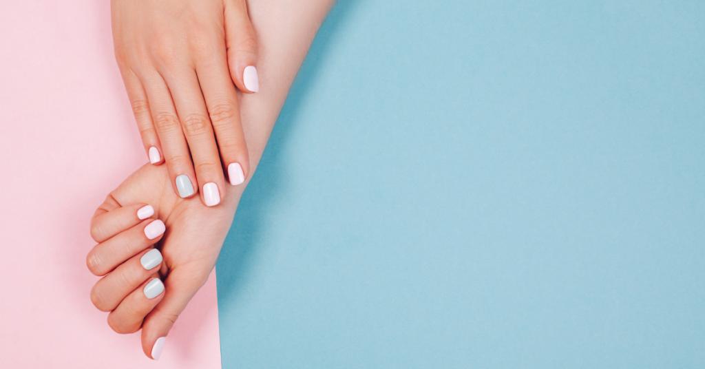 una mano abierta se apoya boca abajo sobre la muñeca de otra mano boca arriba pero con cerrada ambas llevan las manos pintadas con diferentes tonos pasteles rosa y azul