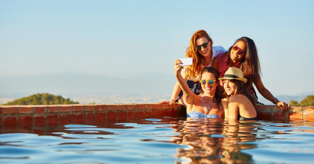 grupo de cuatro chicas jovenes aparecen al fondo de una piscina y se hacen una foto selfie
