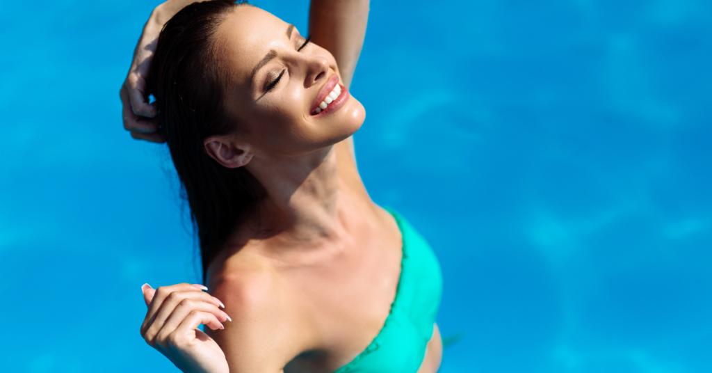 chica en una piscina mira hacia el cielo con los ojos cerrados y una mano sobre el cabello mojado lleva un bikini verde