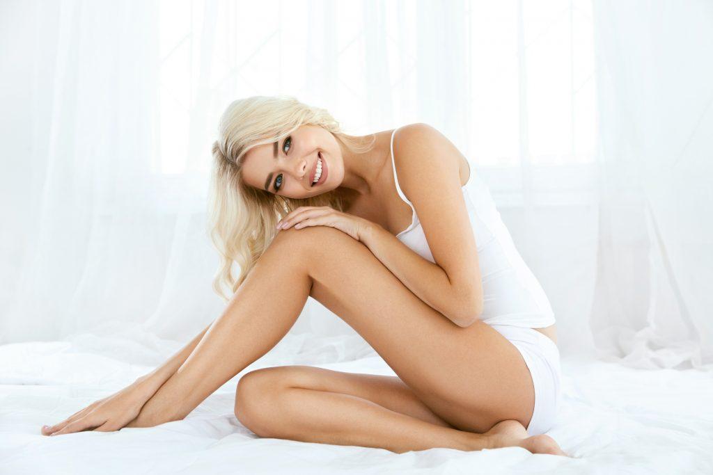 mujer sonriendo es rubia y esta sentada con ropa interior blanca sobre sabanas blancas con la piel depilada