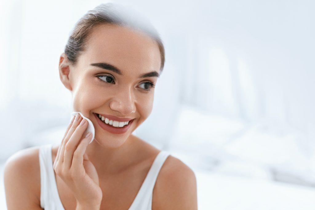 chica joven sonriendo mira hacia su izquierda mientras se toca la barbilla con un algodón blanco