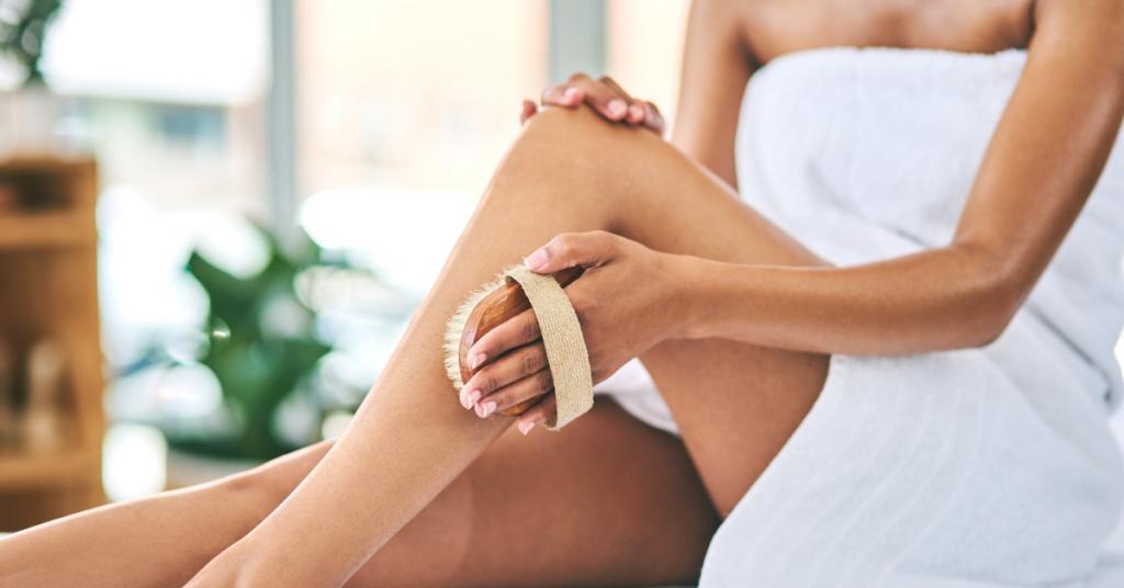 Una mujer pasa una esponja exfoliante por su pierna lleva puesta una toalla blanca