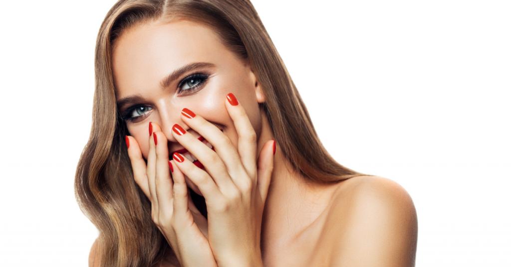 chica joven se rie tapándose la boca con las manos que tienen las uñas pintadas de rojo