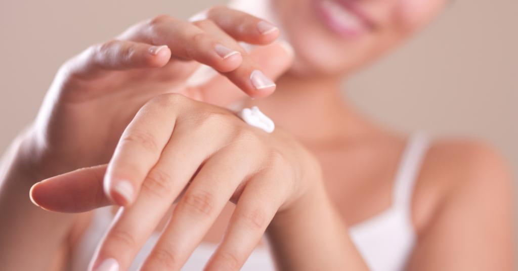 manos de mujer en un primer plano y una mano echa crema sobre la otra