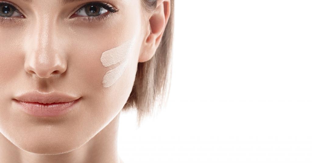 Líneas de crema de tono de piel en la cara de mujer. Hermosa mujer retrato belleza piel sana y maquillaje perfecto. Tiro del estudio Aislado en blanco
