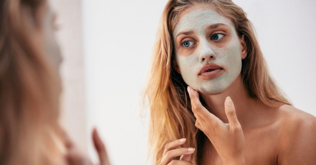 el reflejo de una chica joven en el espejo con el pelo rubio y largo y mascarilla facial en la cara