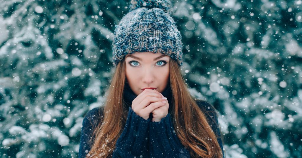 Retrato de Navidad de hermosa niña con sombrero con nieve