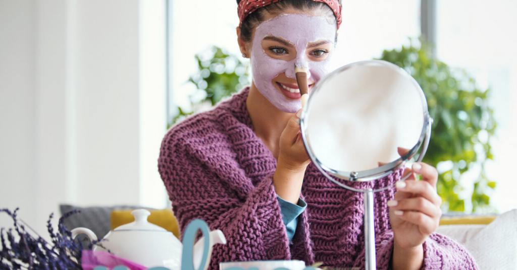 Mujer joven que aplica la máscara facial. Está sentada en su cama mirando al espejo y cuidando su piel durante la mañana del fin de semana.