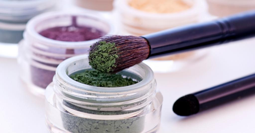 pincel de maquillaje de cerdas morado con polvo verde apoyado sobre un tarro con más polvo verde y en el fondo hay más tarros con polvos de colores