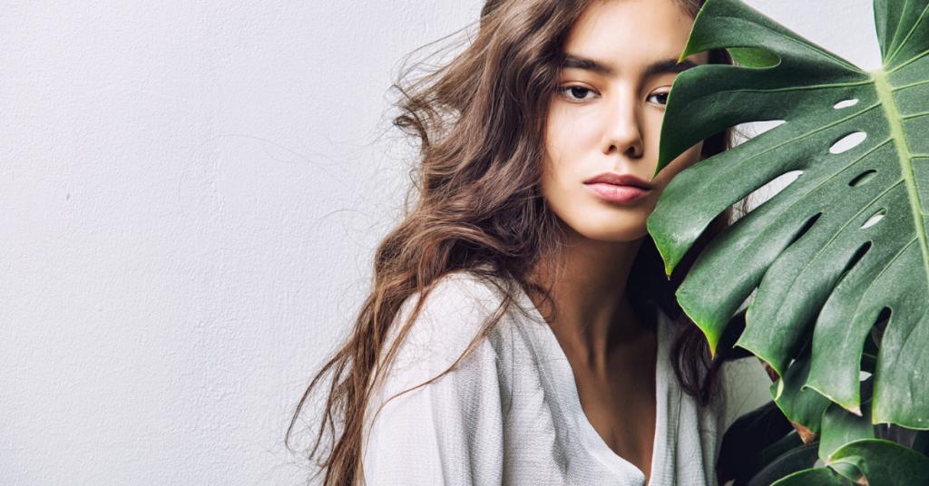 medio plano de una chica joven y seria sobre fondo blanco esconde la mitad del rostro detrás de una planta