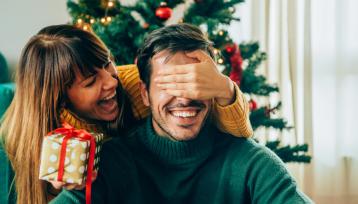 Hermosa joven está de pie detrás de su novio con un regalo en una mano y se cubrió los ojos con la otra mano.