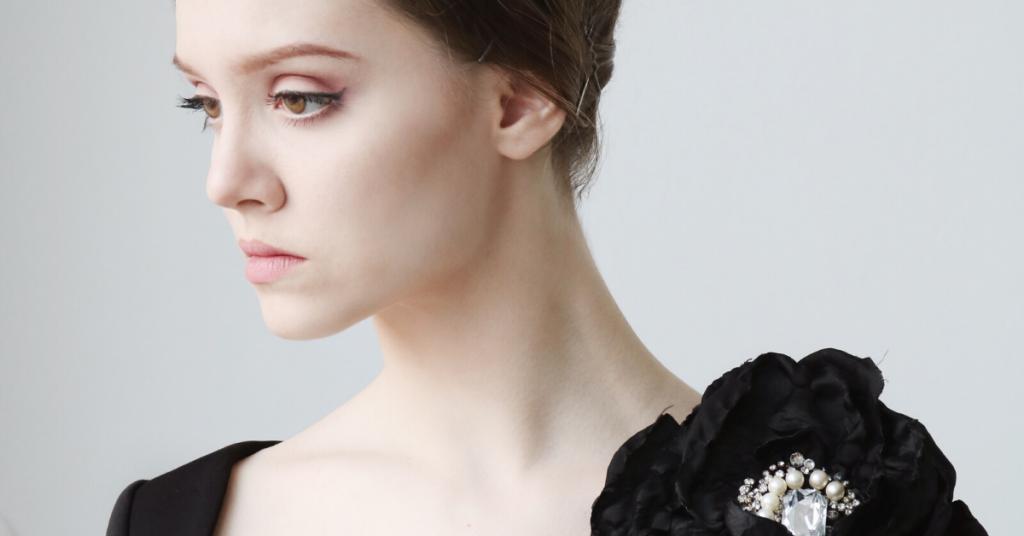 primer plano de una chica joven de tez palida mira de perfil triste y lleva un vestido arreglado de noche