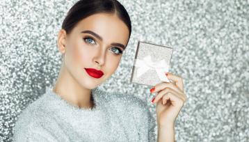 chica joven y guapa con los labios en rojo mira a camara mostrando un pequeño regalo envuelto en glitter plateado sobre dondo plateado tambien brillante