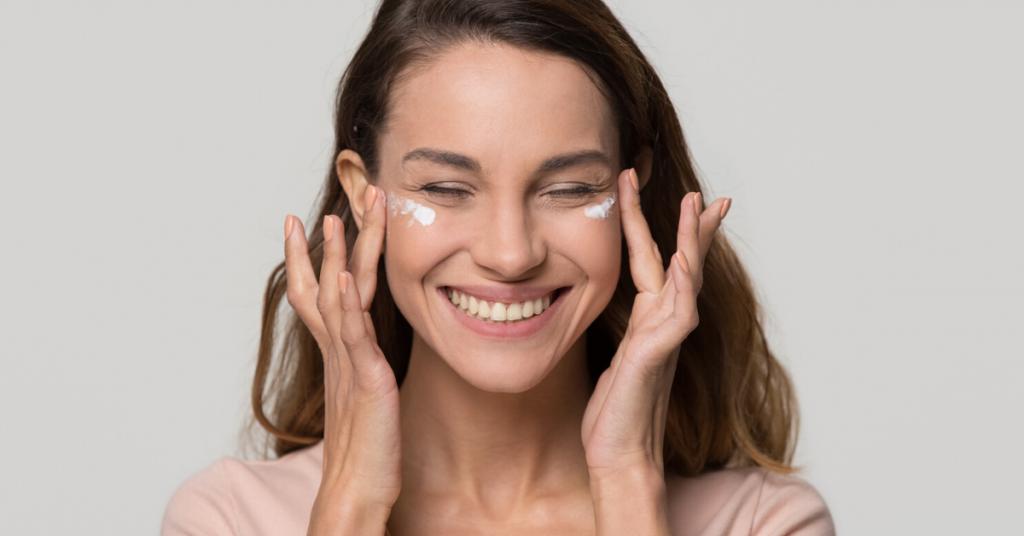 Chica bastante joven sonríe feliz mientras se aplica crema cosmética loción hidratante en la cara para el cuidado de la piel limpia suave y saludable tratamiento de belleza natural aislado sobre fondo gris blanco de estudio