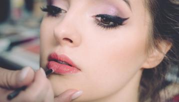 chica joven es maquillada por una mano profesional que le pinta los labios color rosa