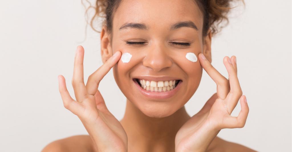Protección de la piel. Muchacha que ríe que aplica la crema hidratante en su cara sobre el fondo blanco