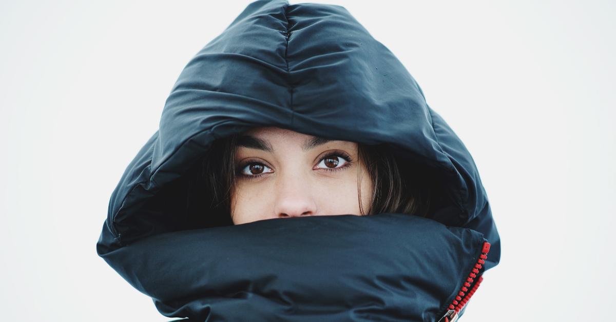 chica joven mira a camara seria lleva un chaquetón tipo plumas con la capucha puesta y el cuello alzado hasta la nariz