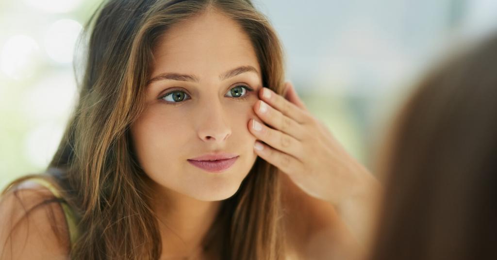 Foto de una mujer joven tocando su piel frente al espejo