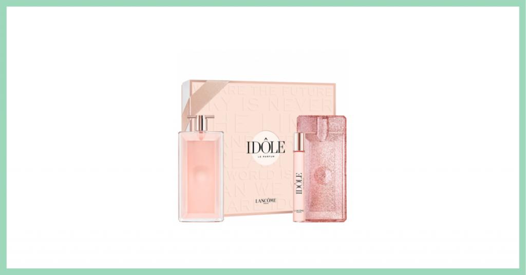 caja rosa con el nombre del perfume que contiene Idole de la marca Lancome junto al frasco de colonia color rosa, un perfume para llevar y una carcasa rosa para proteger perfume