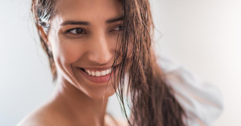 Chica joven de piel morena sonrie mirando de lado con el pelo mojado mientras se lo seca con una toalla