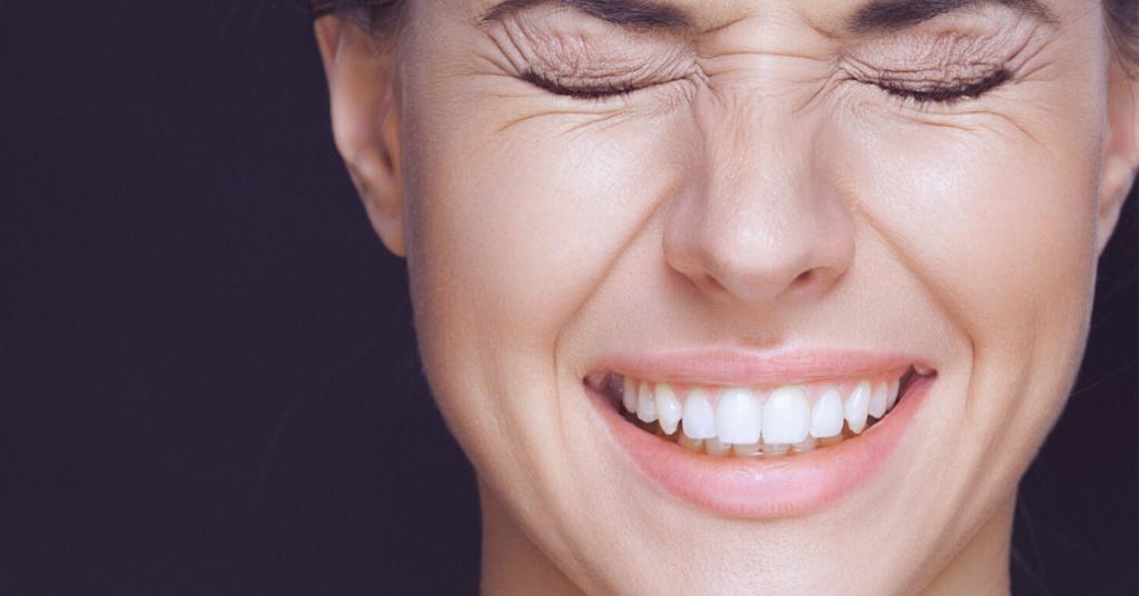 Primer plano de mujer joven con los ojos muy cerrados y la sonrisa para mostrar los tipos de arrugas faciales, cómo tratarlas y amarlas