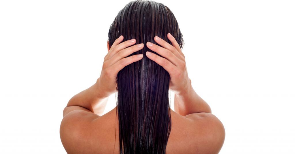 Mujer de espaldas se sujeta la cabeza con el pelo moreno y mojado para ilustrar los 5 errores que todas cometemos con nuestro pelo y cómo solucionarlos