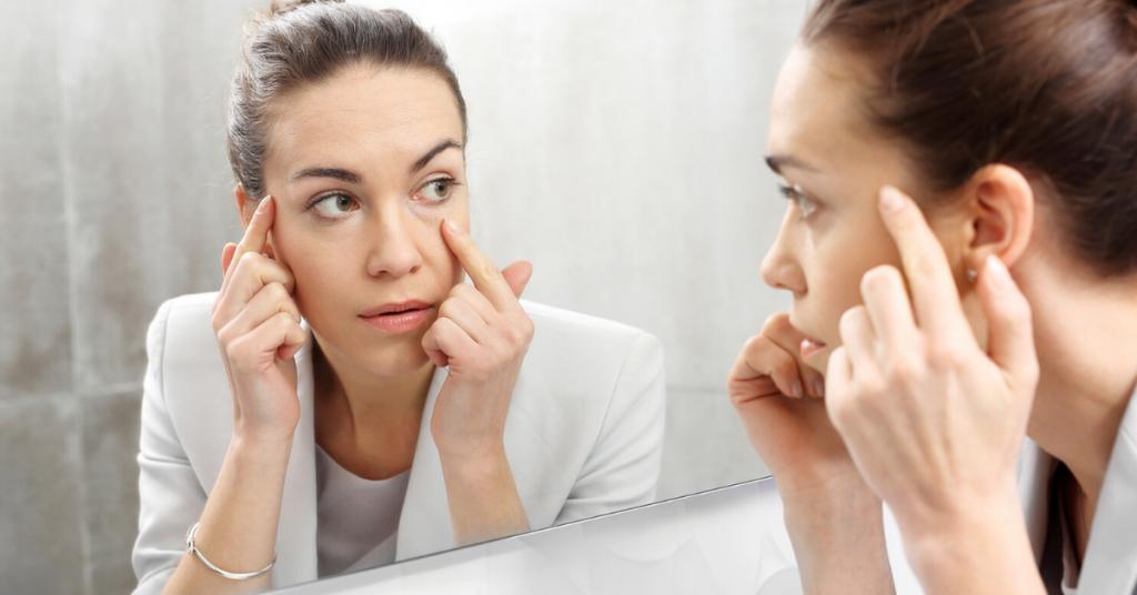 Chica joven con traje de chaqueta gris se mira en un espejo para ver los tipos de arrugas faciales, cómo tratarlas y amarlas