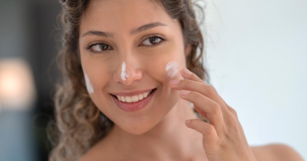 Retrato de una bella mujer en el baño aplicando protector solar en la cara