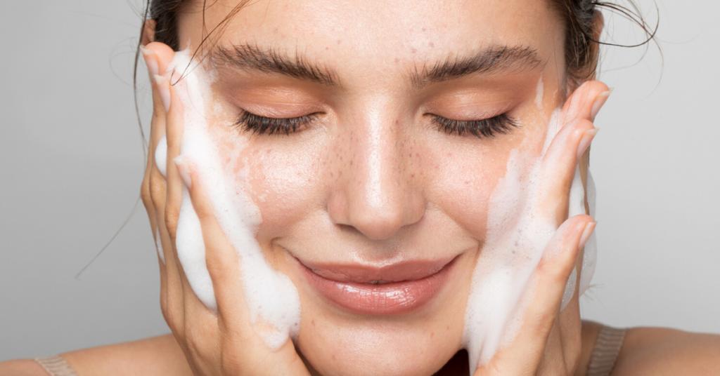 Cerrar foto de estudio de una bella mujer con una piel perfecta, mientras se limpia la cara