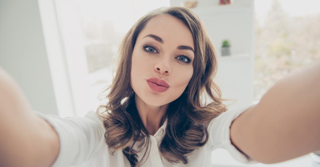 Chica joven y morena con los labios pintados se hace un selfie en este articulo sobre labiales favoritos y qué los hace tan especiales