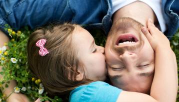 padre joven tiumbado en la hierba es besado por su hija pequeña en la cara mientras él se rie