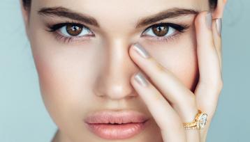 Primerísimo primer plano de una chica joven con la mano en el rostro para mostrar unas uñas sanas que puedes conseguir si sigues los consejos del artículo