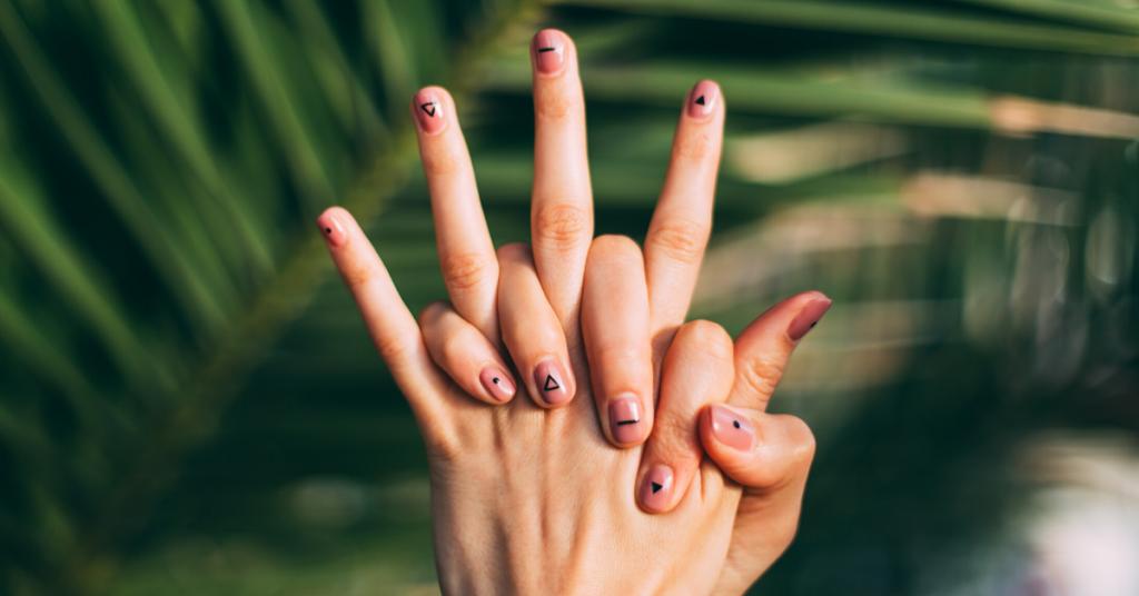 Dos manos sobre un fondo de hojas verdes con las uñas pintadas con dibujos geométricos para mostrar qué sanas y fuertes puedes tener las uñas si sigues los consejos del artículo