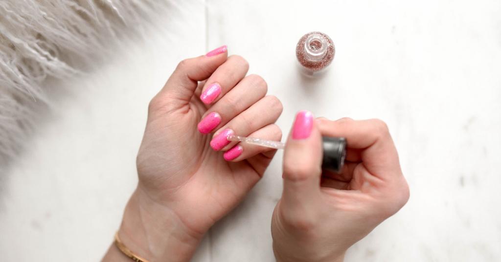 Una mano con las uñas pintadas de rosa y purpurina se pinta las uñas de la otra mano del mismo color para ilustrar cómo de sanas y fuertes vas a tener las uñas si sigues los consejos del artículo