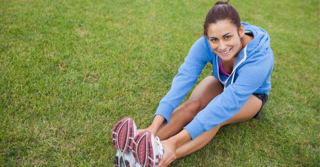 Chica joven vestida con ropa deportiva está sentada sobre el césped con las manos estiradas hasta las zapatillas de deporte para amar su cuerpo y prevenir y tratar los tipos de estrías que existen