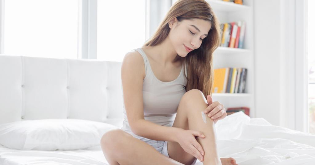 Chica joven se echa crema corporal en las piernas sobre su cama para amar su cuerpo y prevenir y difuminar los diferentes tipos de estrías